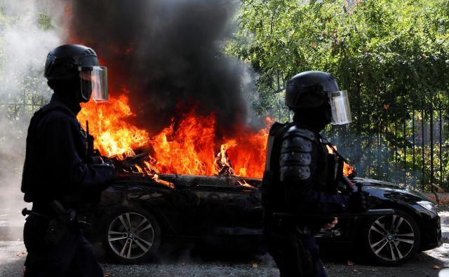 Francoski policisti ob zažganem avtomobilu med današnjim protestom rumenih jopičev v Parizu. FOTO: Gonzalo Fuentes/Reuters