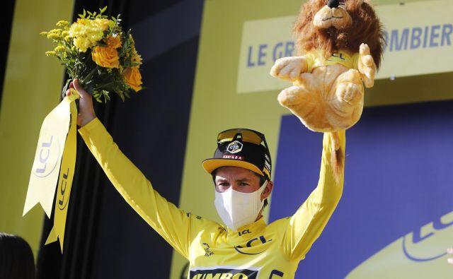 Primož Roglič drži v rokah rumeno majico vodilnega na dirki po Franciji. FOTO: Thibault Camus/Reuters
