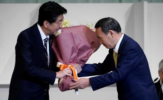 Nekdanji in bodoči premier Japonske Šinzo Abe in Jošihide Suga. FOTO: Eugene Hoshiko/Reuters