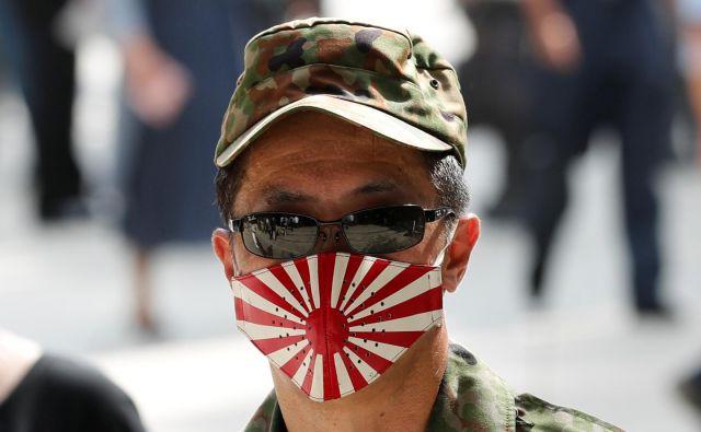 A lej ga šmenta: zarotniški Japonci maske nosijo že najmanj sto let. Že pred toliko leti so vedeli, kaj se bo zgodilo z virusi. Vsaj sto let so vadili, da so danes zarotniki par exellence. FOTO: Kim Kyung Hoon/Reuters