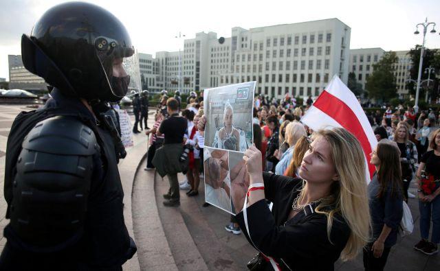 Protestniki zahtevajo razveljavitev volitev in odstop predsednika. Protestnica na sliki policistu kaže fotografijo protetsnice, ki so jo poškodovale varnostne sile. FOTO: izroček Via Reuters