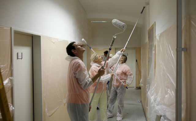 Prostovoljci Novartisa pomagajo barvati sobe v Zavodu Janeza Levca. FOTO: Blaž Samec/Delo
