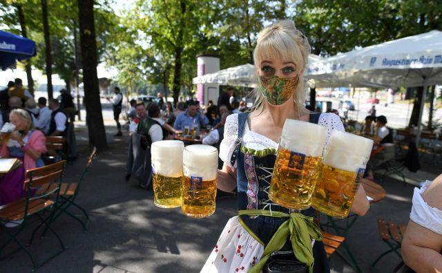 Dekle nosi vrčke na pivskem vrtu blizu Theresienwiese, kjer bi se moral začeti Oktoberfest, a je bil zaradi pandemije odpovedan. Že 187. Oktoberfest bi moral potekati med 19. septembrom in 4. oktobrom. To ni prvič, da je bil Oktoberfest odpovedan, a ga doslej niso pripravili le 24-krat. Odpovedali so ga leta 1854 in 1873 med epidemijo kolere, v obdobju hiperinflacije v 20. letih prejšnjega stoletja ter v času obeh svetovnih vojn. FOTO: Andreas Gebert/Reuters<br />