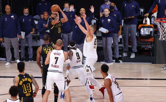 V izjemno razburljivi drugi finalni tekmi zahodne konference med LA Lakers in Denverjem je bil odločilen met Anthonyja Davisa za tri točke dve sekundi pred koncem. Niti odlični Nikola Jokić ni mogel preprečiti koša, po katerem Denver v zmagah zaostaja z 0:2. FOTO: Kevin C. Cox/AFP