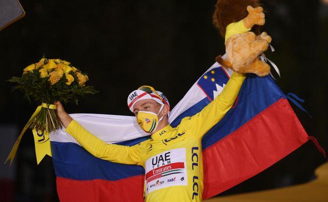 Tadej Pogačar je na odru za zmagovalce Toura raztegnil slovensko trobojnico. Kako bo na SP? FOTO: Marco Bertorello/AFP