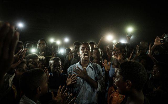 Letošnja zmagovalna fotografija <em>Jasen glas</em> prikazuje mladeniča iz Sudana, ki v Kartumu recitira protestno poezijo. Foto Jasujoši Čiba/AFP