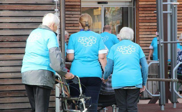 Stanovalci Doma starejših občanov Kočevje z roko v roki na sprehodu, ki ozavešča o problemu demence v Sloveniji. FOTO: Simona Fajfar/Delo