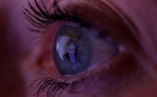 V očesu ženske je moč videti odsev britanskega premierja Borisa Johnsona, ko po televiziji gleda njegov nagovor naciji v Manchestru. FOTO: Phil Noble/Reuters