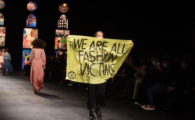 Med modno revijo prestižne znamke Dior, ki je potekala v okviru tedna mode v Parizu, je na pisto pritekla aktivistka z napisom »Vsi smo žrtve modne industrije.« FOTO: Lucas Barioulet/Afp<br /> <br />