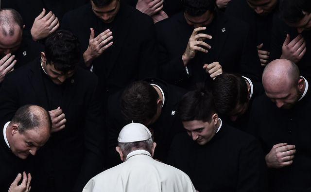 Papež Frančišek moli skupaj z duhovniki pred zaključkom avdience na dvorišču San Damaso v Vatikanu. FOTO: Filippo Monteforte/Afp
