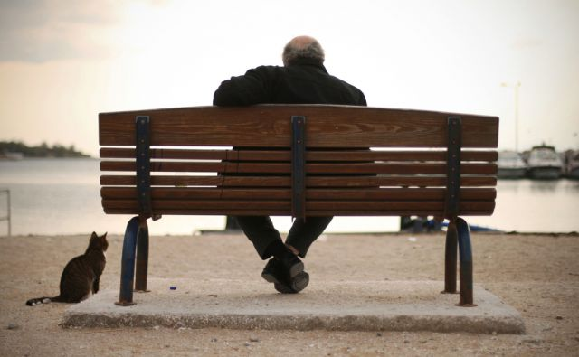 Starejši Atenčan in mačka sedita ob obali in zreta na morje. Grčija se vse bolj brez perspektiv, kot da postaja država tretjega sveta.18.11.2012 Atene, Grčija.