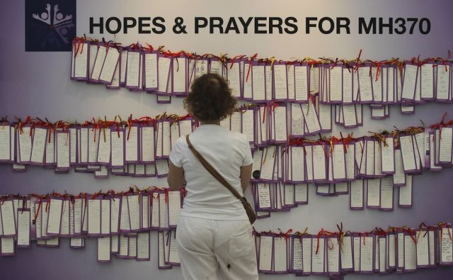 A woman read message cards tied up for passengers aboard a missing Malaysia Airlines plane, in a shopping mall in Kuala Lumpur, Malaysia, Monday, Mar. 24, 2014. A Chinese plane on Monday spotted two white, square-shaped objects in an area identified by