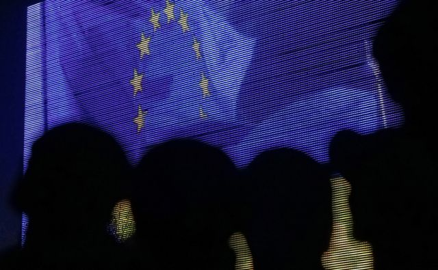 People are silhouetted against a screen showing the European Union flag as they attend a rally in support of euro integration in central Kiev November 22, 2013. The European Union on Thursday expressed disappointment with Ukraine's decision to abruptly
