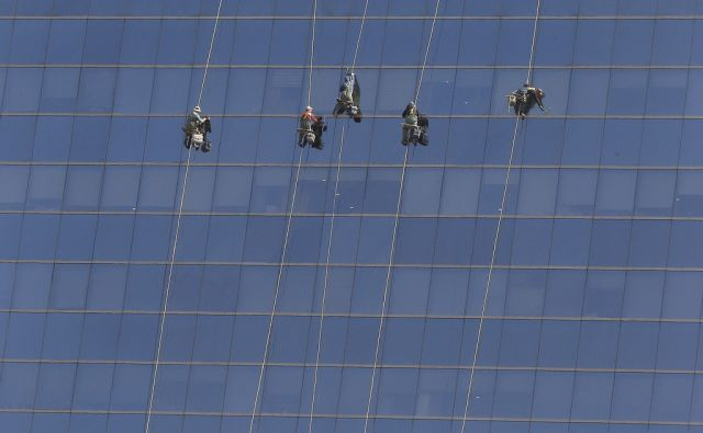 South Korean workers clean windows of an office building ahead of the coming of Spring, in Seoul, South Korea, Wednesday, March 25, 2015. (AP Photo/Ahn Young-joon)