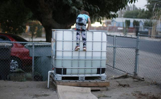 Abigail Beltran, 6, whose family's well has run dry, climbs on a water storage tank in her front yard in Porterville, California October 14, 2014. In one of the towns hardest hit by California's drought, the only way some residents can get water to flush