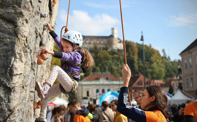 Deklica se z inštruktorico uči plezanja na balvanski steni med Olimpijskim Festivalom na Kongresnem trgu v Ljubljani, Slovenija 17.oktobra 2015. Vodilne teme festivala so šport, ustvarjalnost, povezovanje in druženje. [plezanje,balvanske