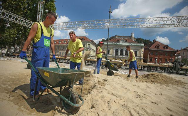 Gradbeni delavci na improviziranem igrišču z mivko na Kongresnem trgu v Ljubljani 8.avgusta 2014.