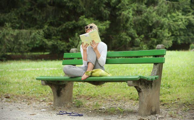 Branje knjige na klopi v parku. Ljubljana, Slovenija, 10.avgusta 2015. [branje, knjige, študenti, mestni parki, Ljubljana, Slovenija, lesene klopi]