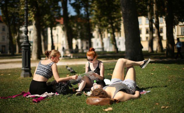 Mladi se družijo, berejo in poležavajo na Konresnem trgu - Parku Zvezda. Ljubljana, Slovenija 3.avgusta 2016. [mladi,mestni parki,Kongresni trg,Park Zvezda,druženje,branje knjig,zemljevidi,turisti,turizem,poletje,vročina,motivi]