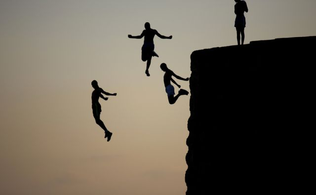 Israeli Arab boys jump into the Mediterranean sea from the ancient wall surrounding the old city of Acre, northern Israel, Tuesday, Aug. 2, 2016. (AP Photo/Ariel Schalit)