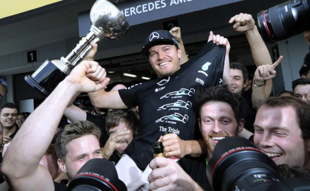 Mercedes driver Nico Rosberg of Germany, center, celebrates after winning the Japanese Formula One Grand Prix with his team members at the Suzuka International Circuit in Suzuka, central Japan, Sunday, Oct. 9, 2016. (AP Photo/Eugene Hoshiko)