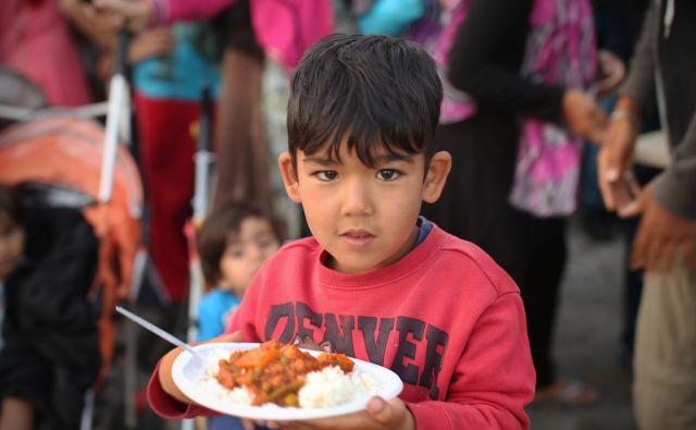 Begunci ob delitvi hrane v pristanišču Pirej v Atenah. Več tisoč jih tu živi v šotorih in v zapuščenem hangarju že od zapore balkanske poti.Atene, Grčija 28.aprila