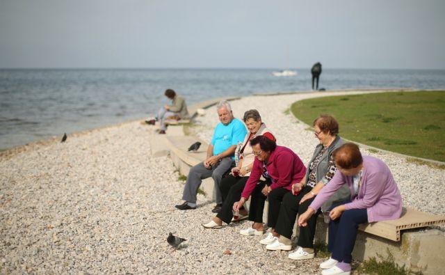 Upokojenci posedajo in uživajo na obali Izole, Slovenija 2.novembra 2016. [upokojenci,starejši,prosti čas,druženje,sprostitev,izleti,morje,obala,Izola,motivi]
