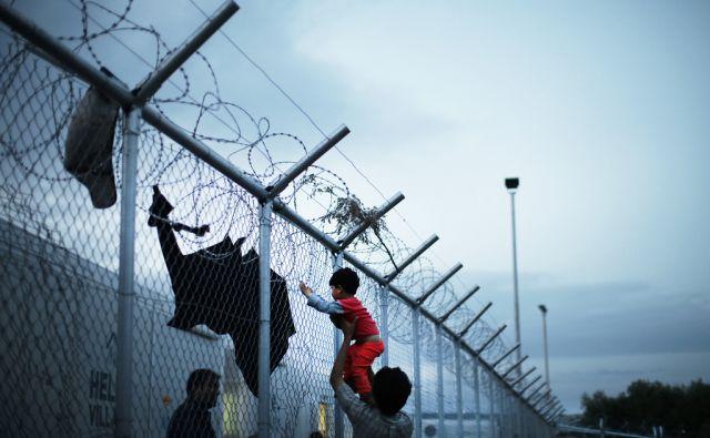 Begunci ob ogradi namestitvenega centra VIAL na otoku Hios. Grčija 2.maja 2016. [Grčija,Hios,begunci,otroci,deček,žičnate ograje,bodeče žice,begunski centri,namestitveni centri,motivi]