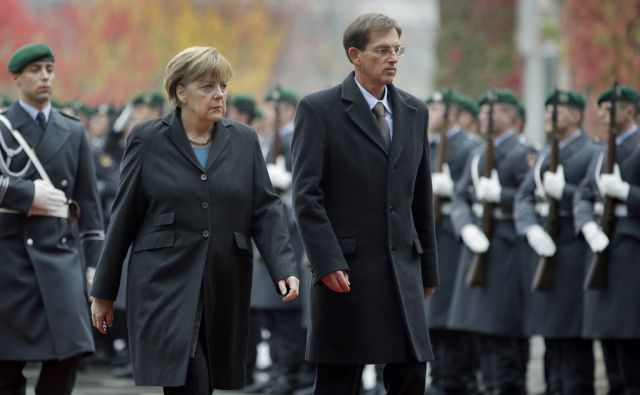 German Chancellor Angela Merkel, left, welcomes the Prime Minister of Slovenia, Miro Cerar, right, with military honors at the chancellery in Berlin, Germany, Thursday, Oct. 30, 2014. (AP Photo/Michael Sohn)