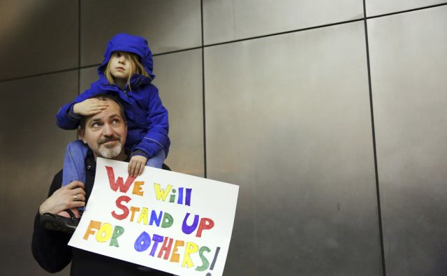 Matt Sernett holds his daughter Wade, 5, atop his shoulders, as more than 1,000 people gather at Seattle-Tacoma International Airport, Saturday, January 28 to protest President Trump's immigration ban.  President Trump signed an executive order Friday