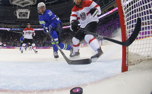 Slovenia forward Jan Mursak scores a shorthanded goal against Austria defenseman Gerhard Unterluggauer in the third period of a men's ice hockey game at the 2014 Winter Olympics, Tuesday, Feb. 18, 2014, in Sochi, Russia. Slovenia won 4-0 to advance to