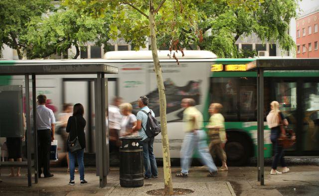 Čakajoči na postajališču Ljubljanskega potniškega prometa - LPP pri Kozolcu.Ljubljana, Slovenija 26.julija 2016 [Ljubljanski potniški promet, LPP,promet,ulice,ljudje,drevesa,zelenje,koši za odpadke]