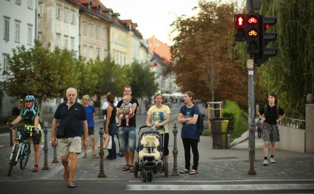 Pri semaforju na Bregu, ob Zoisovi cesti v Ljubljani. Ljubljana, Slovenija 29.avgusta 2017 [ljudje,Ljubljančani,turisti,turizem,pešci,kolesarji,otroci,moški,ženske,družine,starejši,mladi,otroški vozički,promet,semaforji,prehodi za