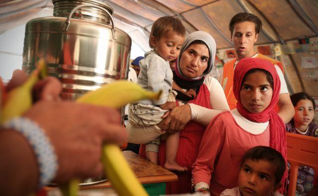 Begunci v vrsti za hrano. V pristanišču Pirej v Atenah jih nekaj tisoč živi v šotorih in v zapuščenem hangarju že od zapore balkanske poti.Atene, Grčija 28.aprila 2016. [Grčija,Atene,Pirej,begunci,ženske,otroci,otroške