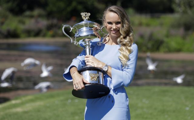Denmark's Caroline Wozniacki poses with her Australian Open trophy, the Daphne Akhurst Memorial Cup in the Royal Botanical Gardens in Melbourne, Australia, Sunday, Jan. 28, 2018. Wozniacki defeated Romania's Simona Halep 7-6, 3-6, 6-4 in Saturday's