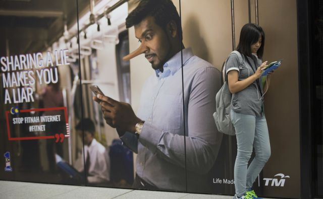 Commuter waiting for subway reading from her phone next to an advertisement discouraging the dissemination of fake news at a train station in Kuala Lumpur, Malaysia, Thursday, March 29, 2018. Malaysia's government has cut the punishment for fake news
