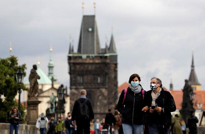 Ljudje z maskami na praškem Karlovem mostu. FOTO:David W. Cerny/Reuters